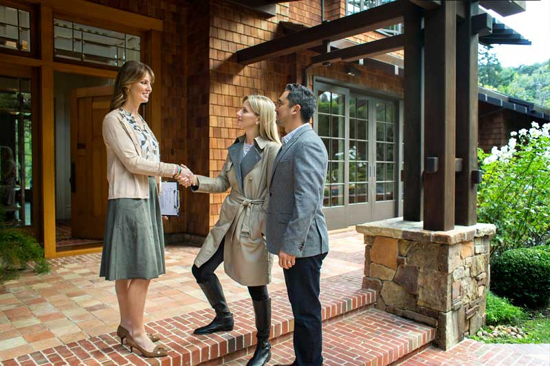 Realtor shaking hands outside a home