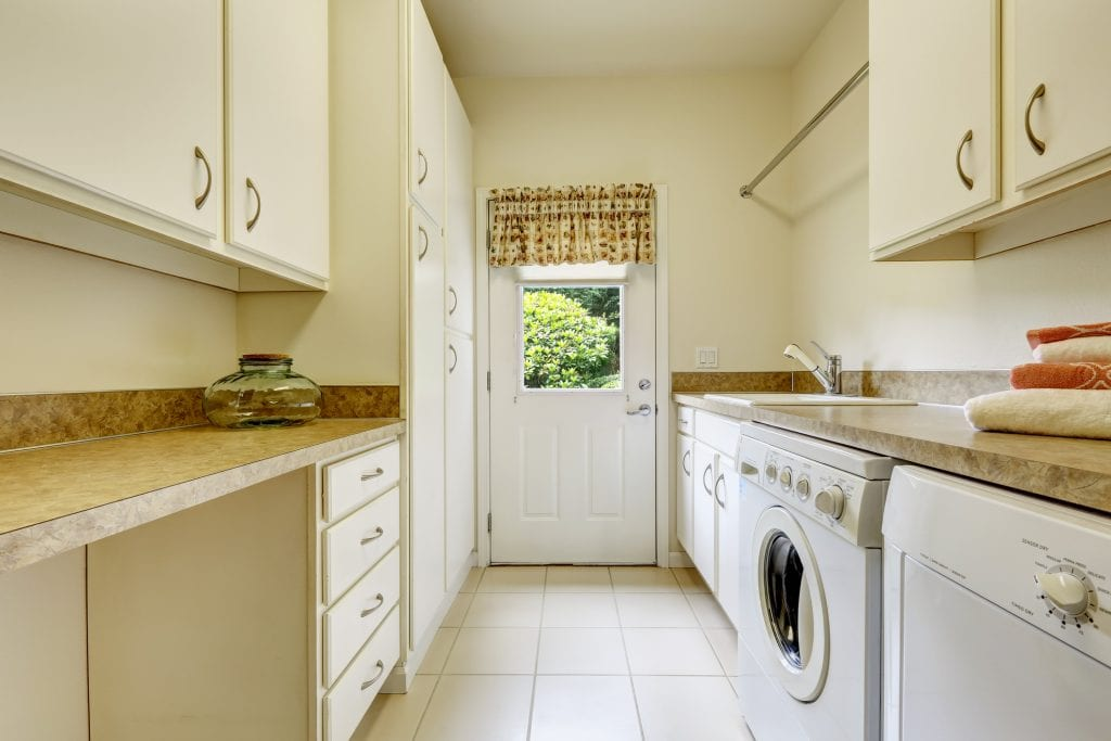 Bright laundry room with white cabinets and appliances