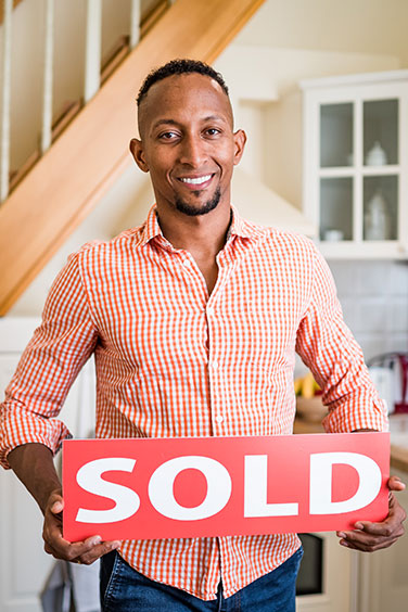 man holding sold sign