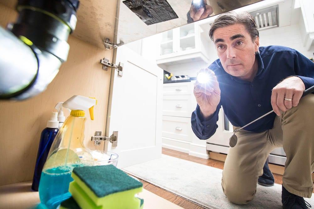 Pillar to Post inspector checking under kitchen sink