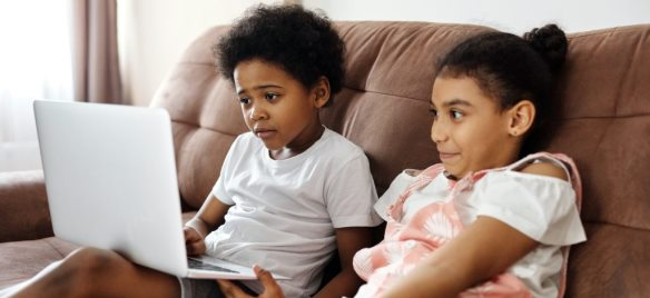 Two kids on the couch looking at a laptop screen